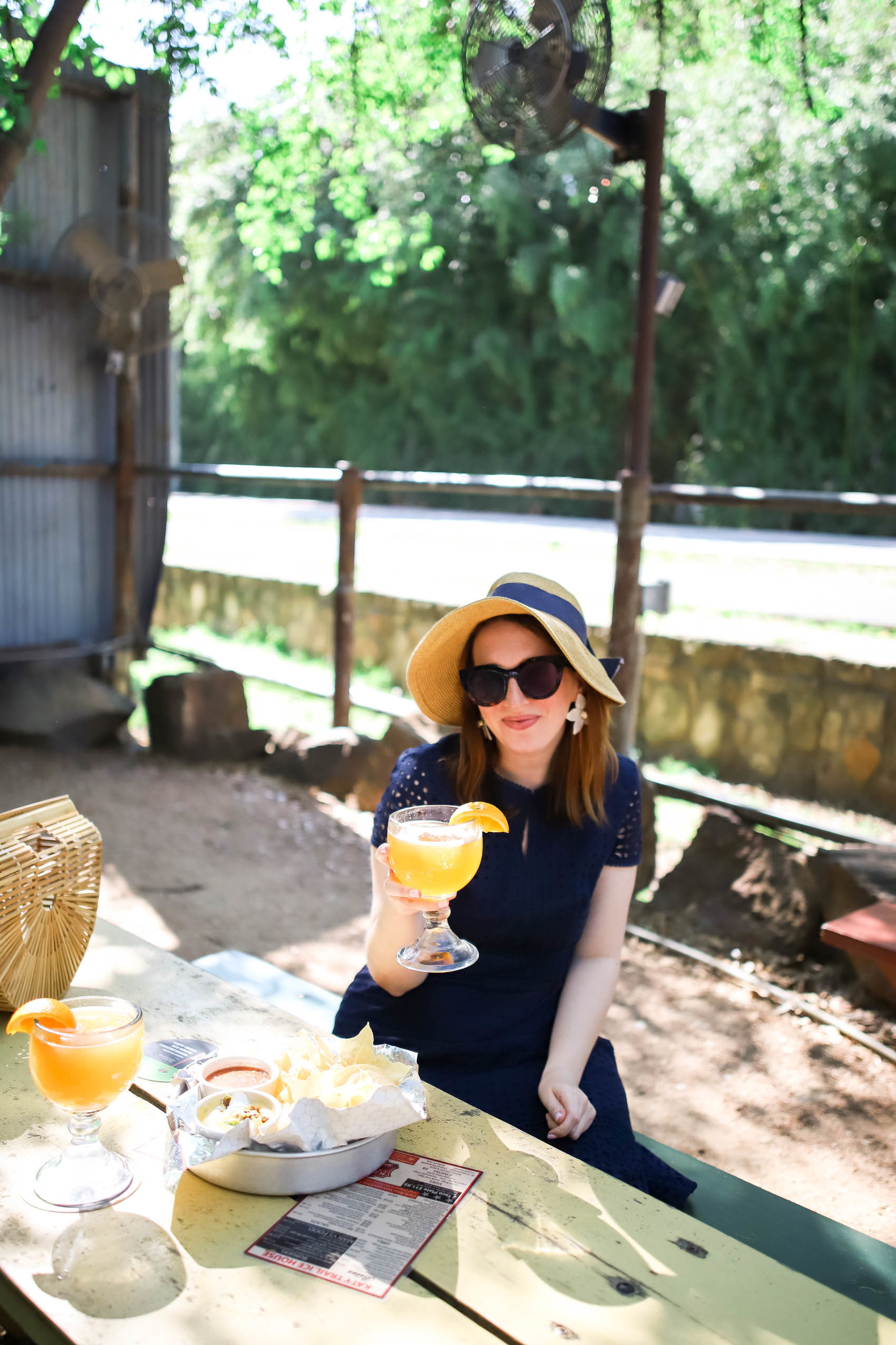 Amanda of Glitter & Spice, holding Revolver Blood & Honey beer at Katy Trail Ice House in Uptown, Dallas | Best Patio Restaurants in Dallas #dallas