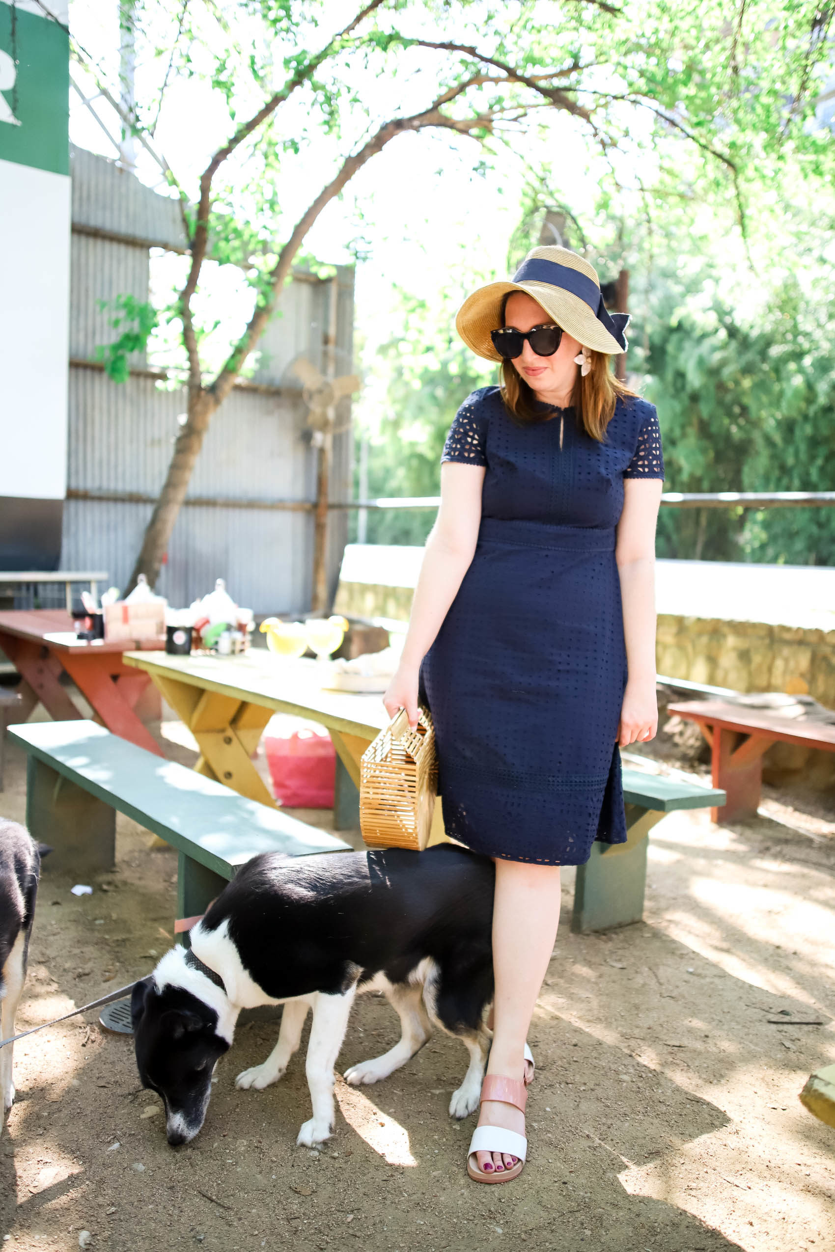 Navy eyelet dress and wide brim hat with navy bow detail | What to wear to a picnic | What to wear to a patio restaurant | What to wear in Dallas in the Spring #dallas #spring #outfit
