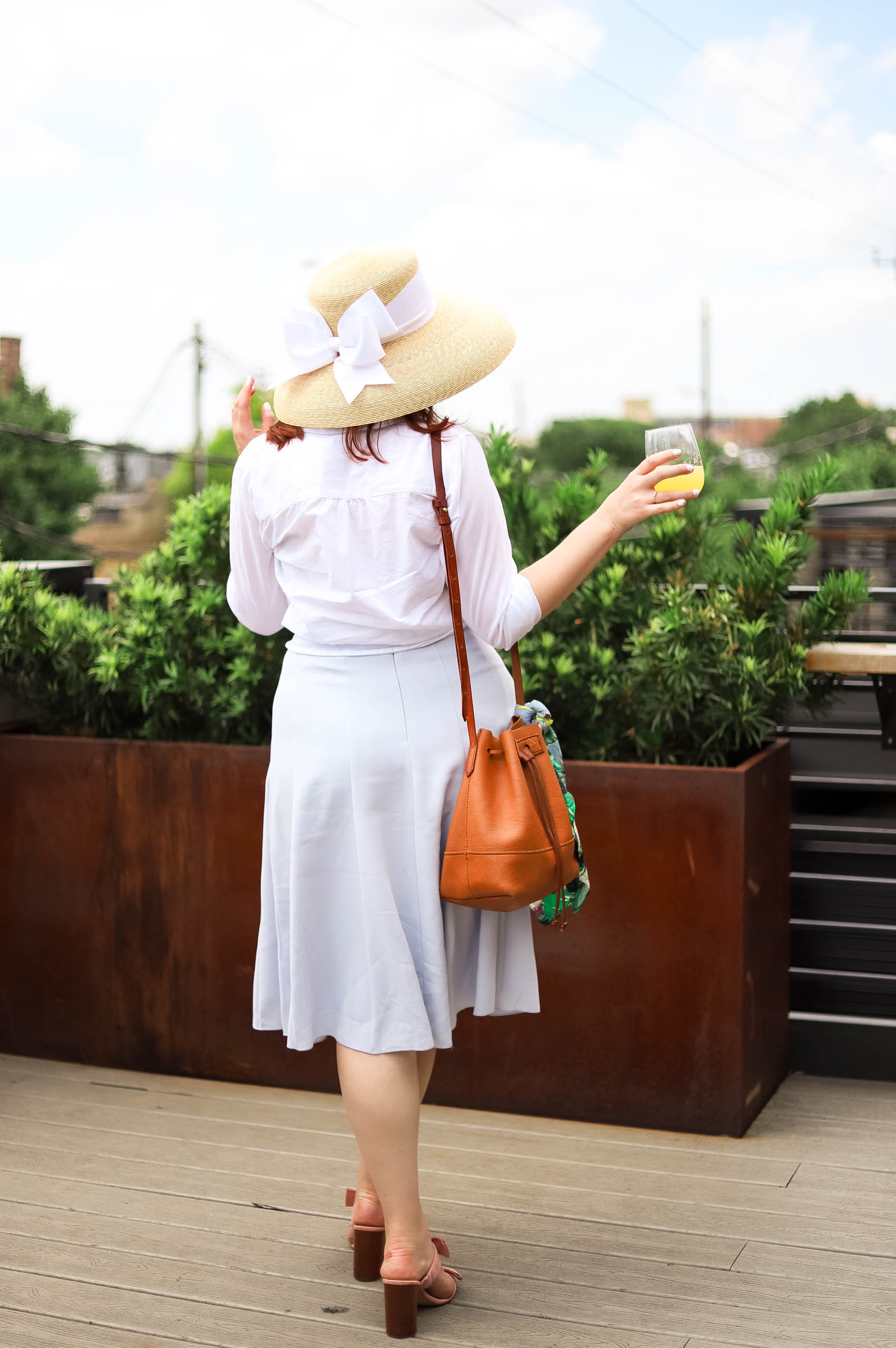 Blogger shares story about how to mend a broken relationship while posting with hat with a white bow, knee-length blue skirt, and a bucket bag.