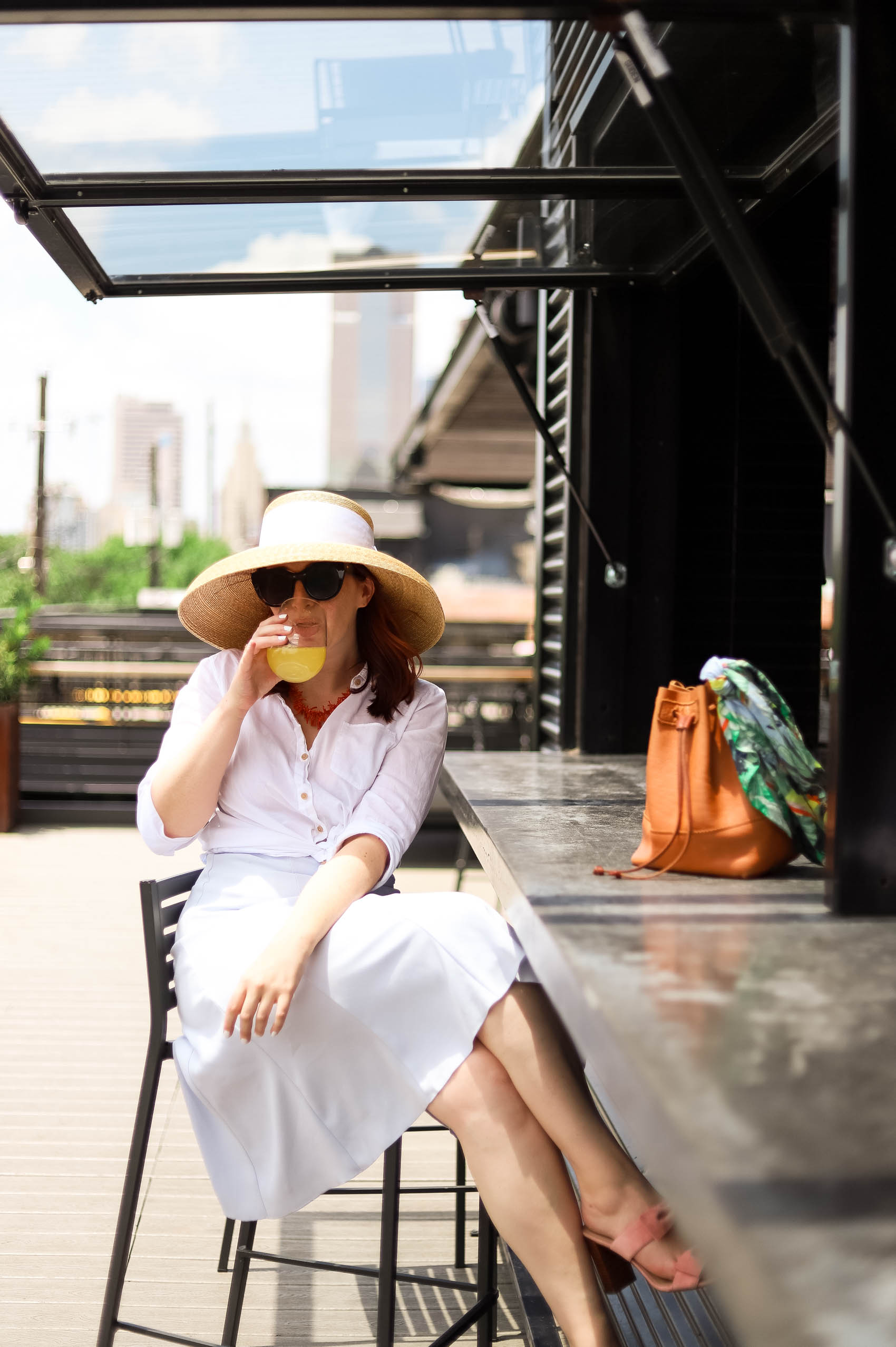Wearing linen blouse and blue shirt, sharing story about fixing relationships while drinking mimosa on a patio