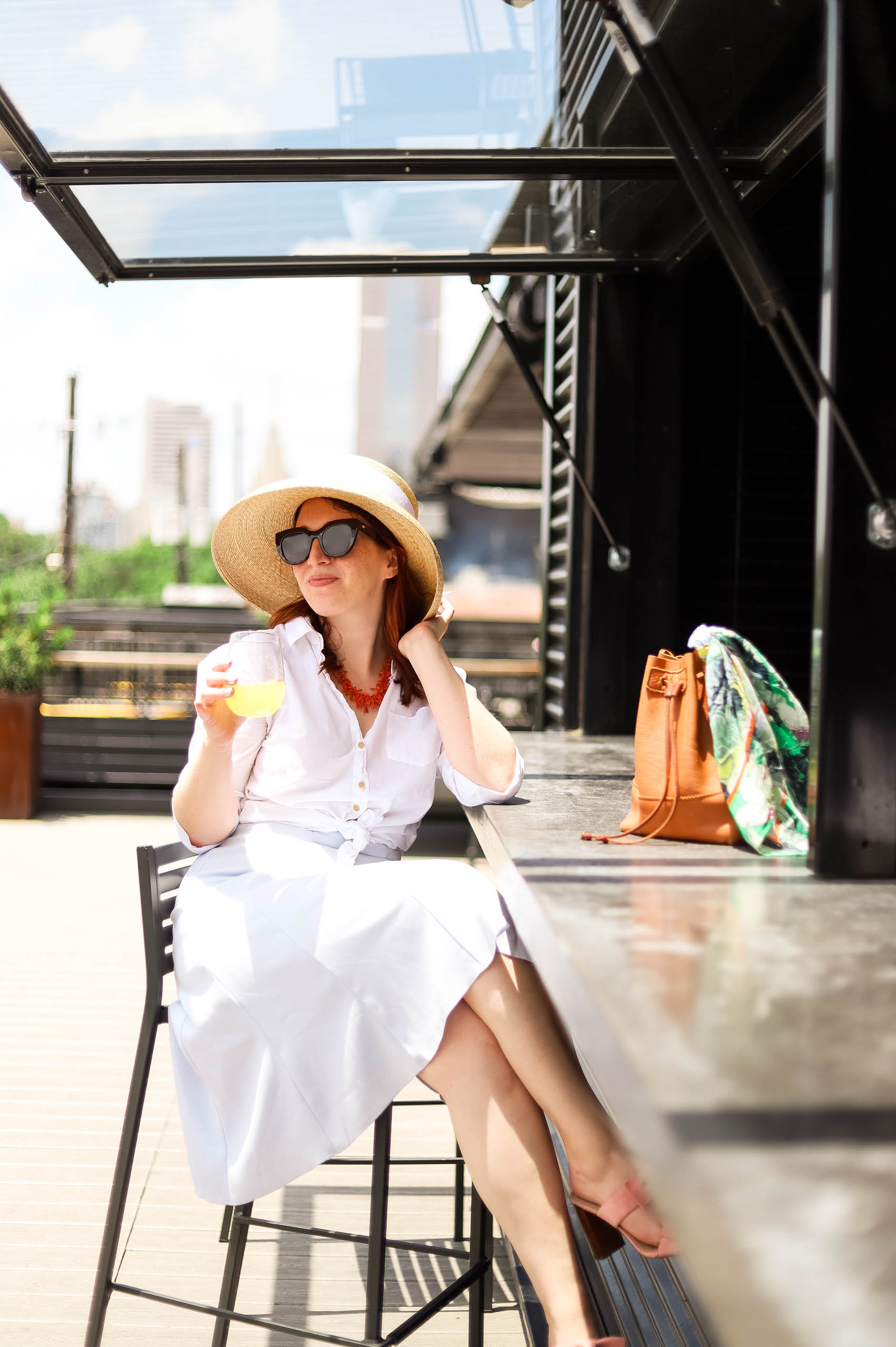 Blogger sharing story about how to mend a broken friendship while wearing summer outfit (knee-length skirt, J.Crew linen shirt, and bow hat).