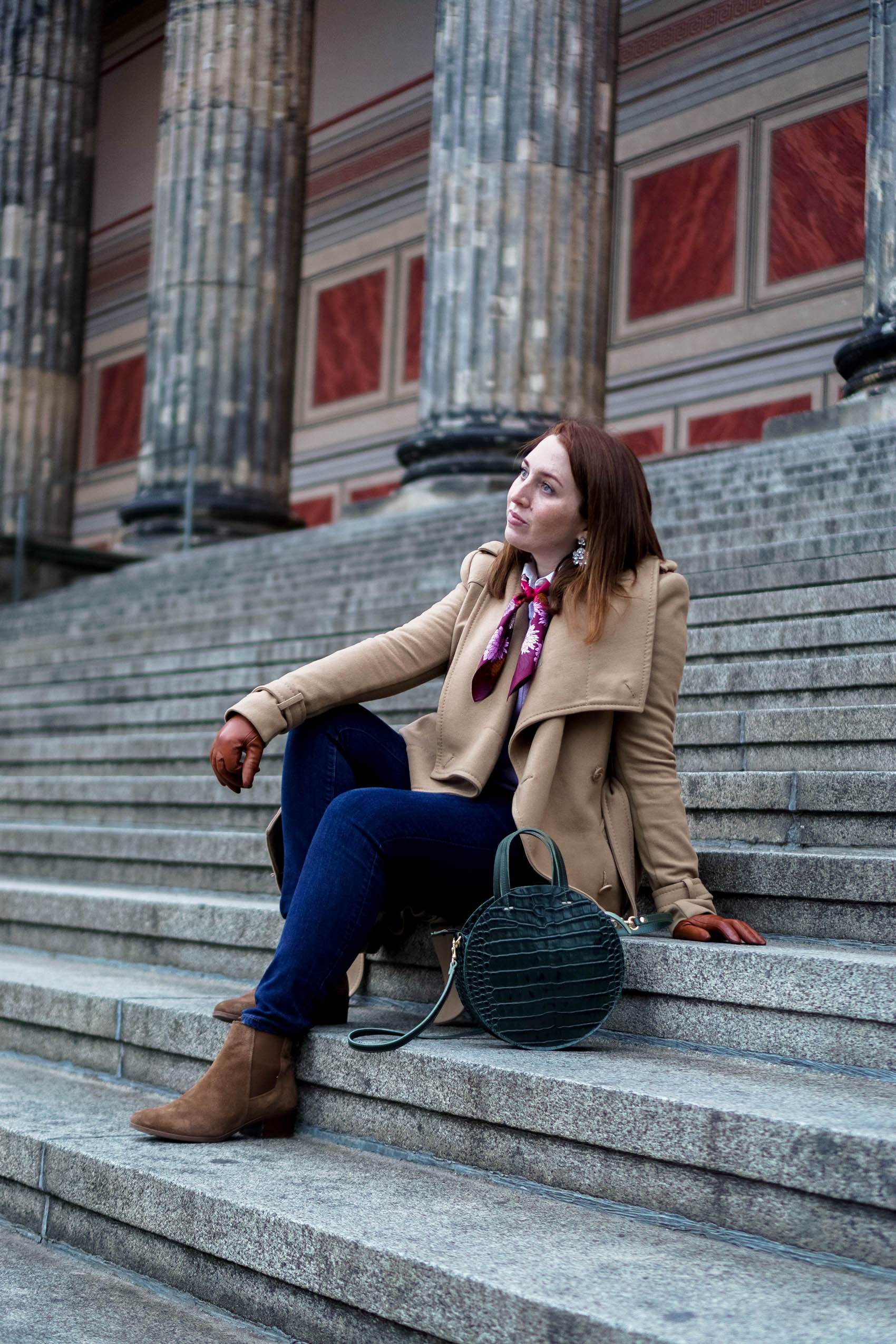 Girl in camel coat on steps in Berlin