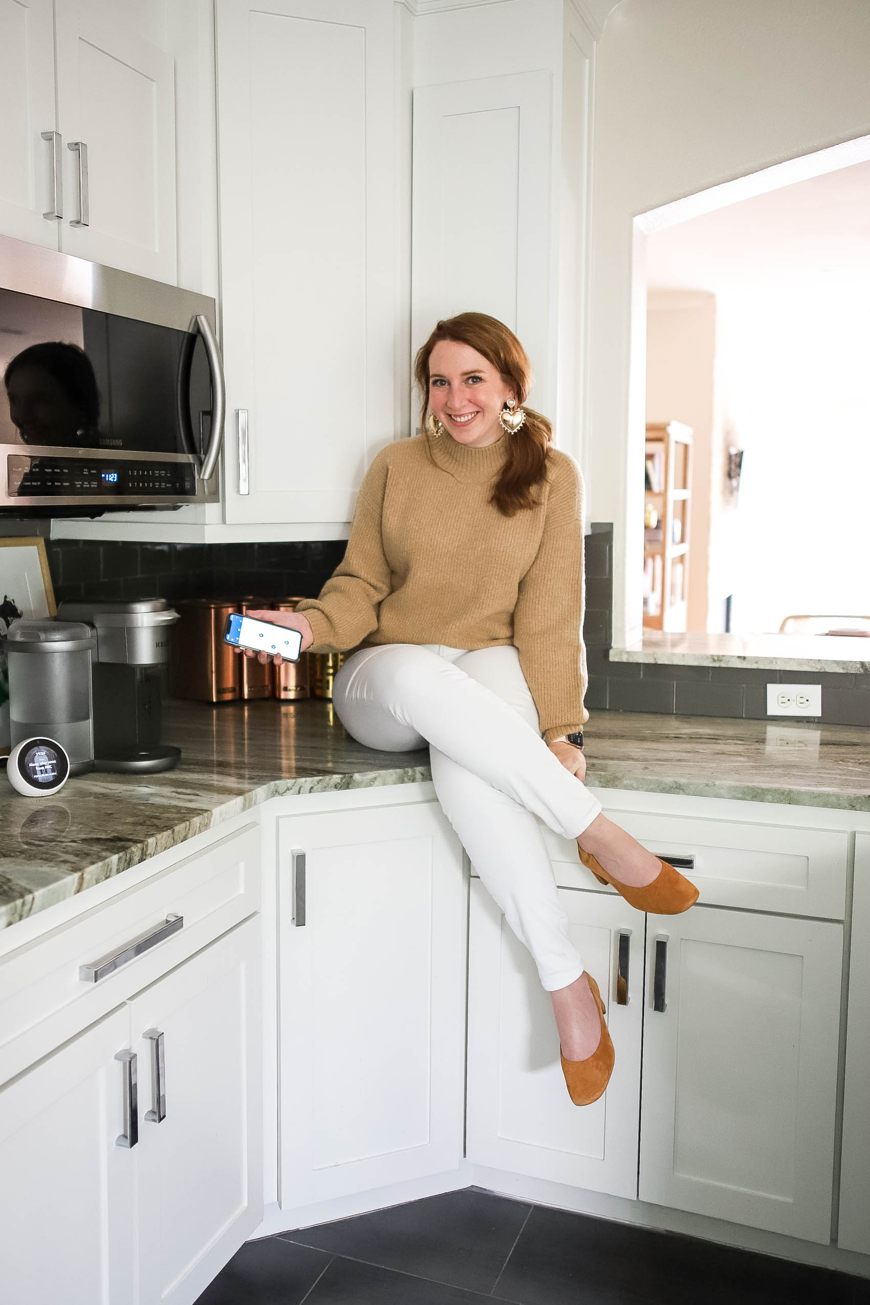 Blogger sharing favorite smart home devices while sitting on kitchen counter, wearing fall outfit comprised of camel-colored mock neck sweater, white jeans, and block heels.