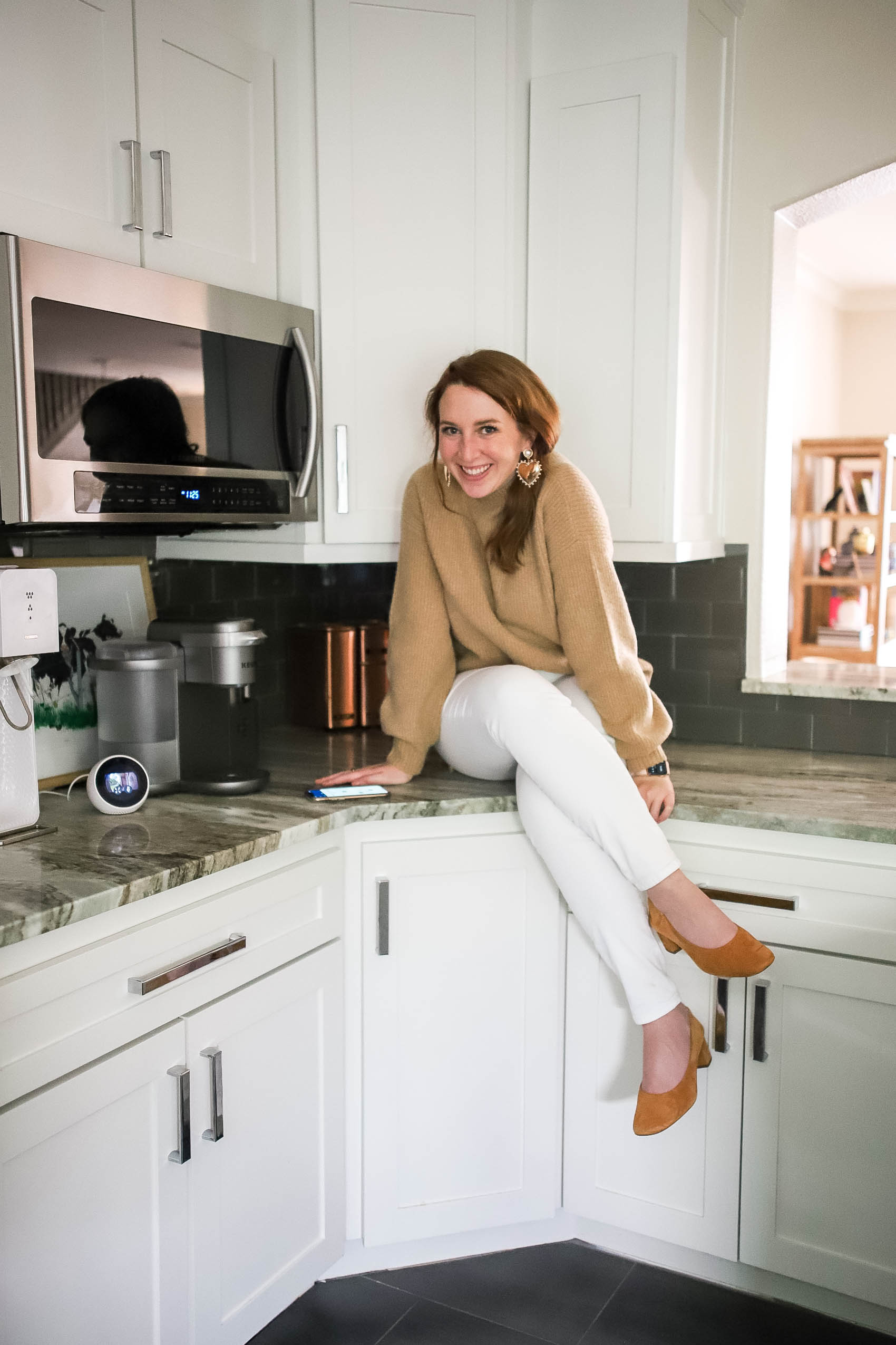 Blogger sitting on counter, wearing camel mock neck sweater, statement earrings, white jeans, and block heels (Everlane The Day Heel).