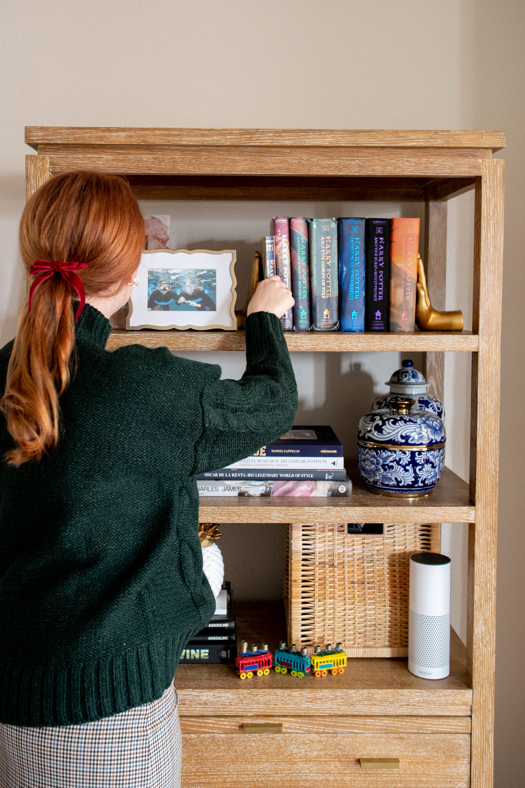 Girl with red hair and red bow in her hair wearing a green cable knit sweater styles bookshelf as example outfit from a winter capsule wardrobe
