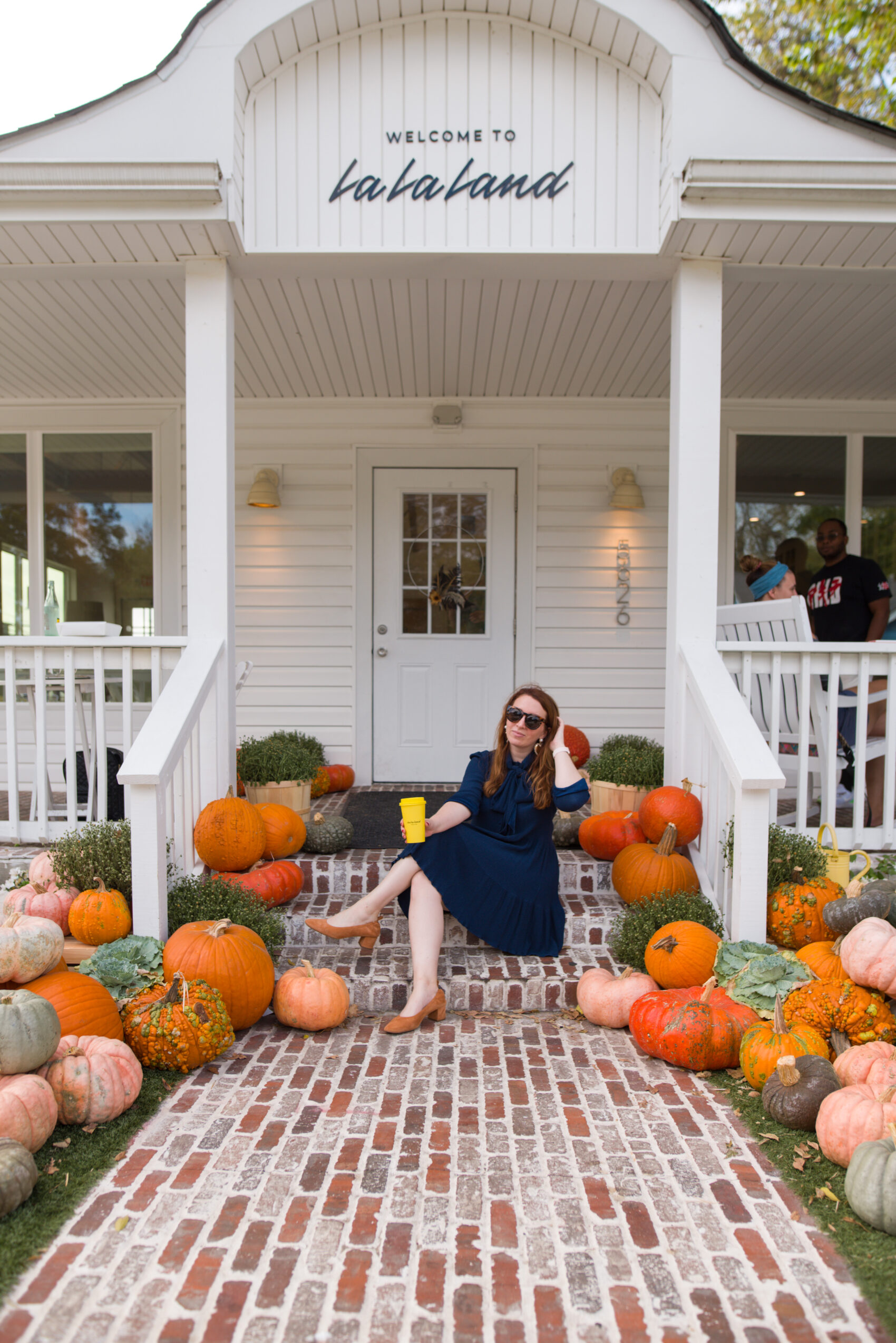 Dallas blogger's list of the best local coffee shops - photo features blogger sitting on the Lower Greenville location of La La Land Kind Cafe's porch