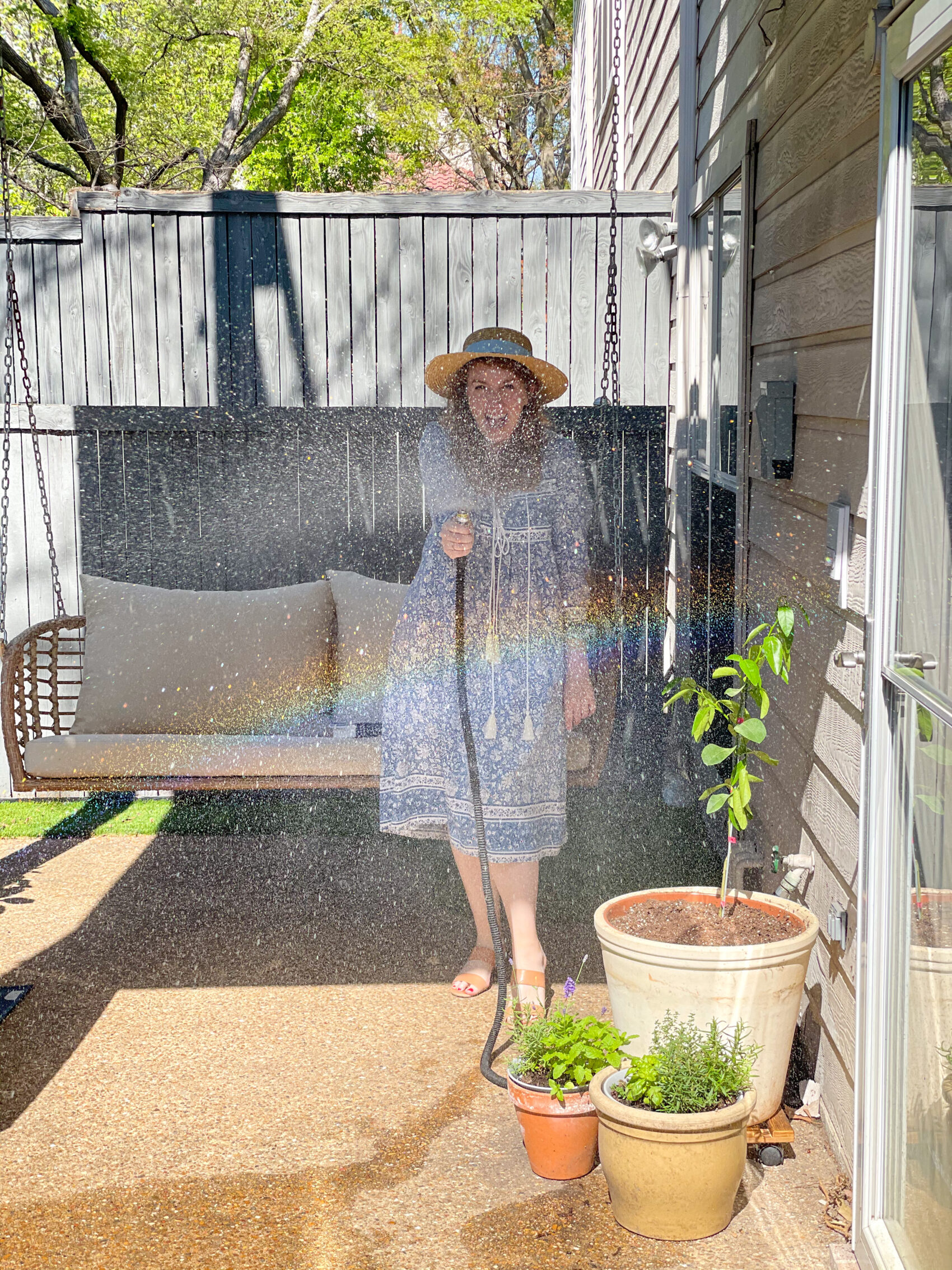Blogger Amanda Kushner watering her herb garden as part of her outdoor living space reveal photos.