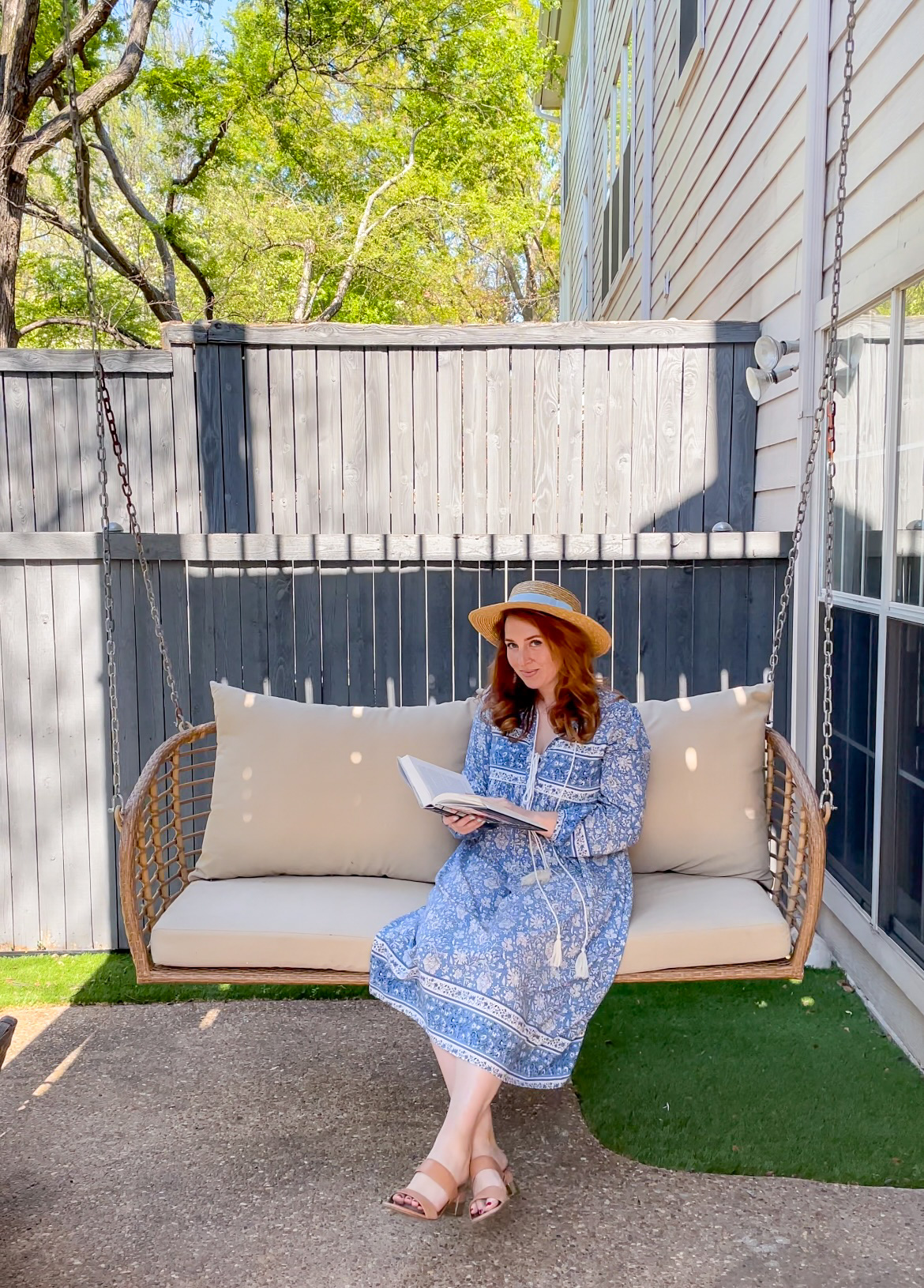 Blogger Amanda Kushner, wearing boater hat and a blue nap dress, sits on a patio swing while reading a book.